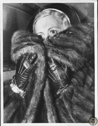 Мэй Капоне, жена знаменитого гангстера Аль Капоне, кутается в меха, пытаясь скрыться от камер журналистов во время посещения мужа в тюрьме Алькатрас, 1929 год Мэй, девушка из уважаемой