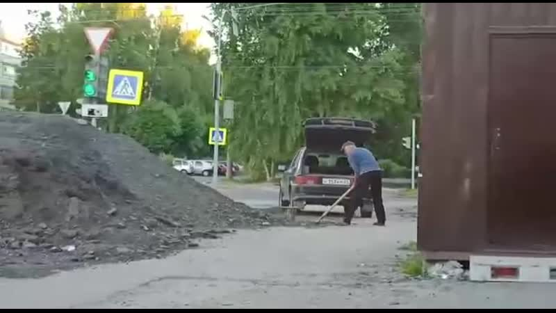 Мужчина грузит в багажник асфальтную крошку