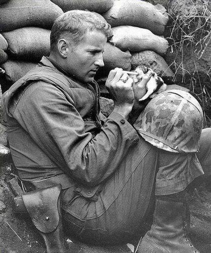 Сержант морской пехоты Фрэнк Прейтор с помощью пипетки кормит молоком маленького котенка, мама которого погибла от мины 1953 г.,